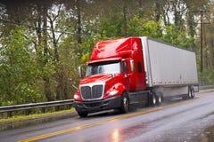 Modern red glossy in rain semi truck trailer on raining road Stock Image