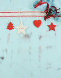 Modern red and white hanging Christmas decorations on aqua blue wood background. Vertical. Royalty Free Stock Photo