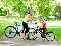 Mom and daughter give high five while cycling in the park Stock Photos