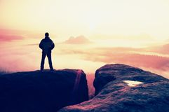 Moment of loneliness. Man on the rock empires  and watch over the misty and foggy morning valley to Sun Royalty Free Stock Photo