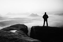 Moment of loneliness. Man on the rock empires  and watch over the misty and foggy morning valley to Sun Royalty Free Stock Photos