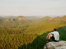 Moment of loneliness. Man in shirt sit on the cliff of rock and watching into forest valley. Stock Images