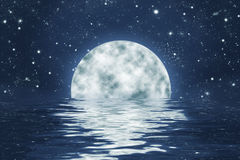 Moonset over ocean with full moon on blue night sky Royalty Free Stock Photography