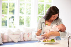 Mother With Baby Eating Healthy Meal In Kitchen Royalty Free Stock Images