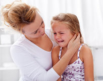 Mother comforting her crying little girl Stock Photos