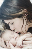 Mother kissing newborn baby Stock Image