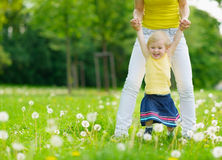 Mother playing with baby girl on dandelions field Stock Image