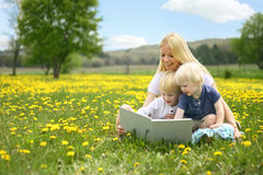 Mother Reading Story Book to Two Young Children Outside in Meado Royalty Free Stock Images