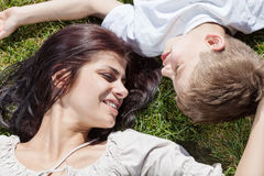Mother and son lying on the grass head to head Stock Photography