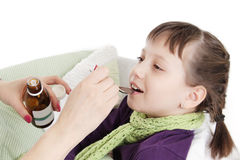 Mothre giving spoon dose of medicine to child Stock Photos