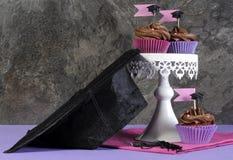 Muffin för parti för rosa färger och för lilor för avläggande av examendag på tappning står Arkivbilder