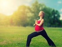 Mujer embarazada sana que hace yoga en naturaleza Fotos de archivo libres de regalías