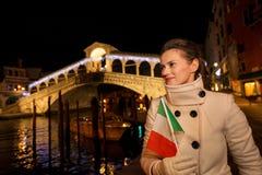 Mulher com a bandeira italiana que tem o tempo do Natal do divertimento em Veneza Foto de Stock