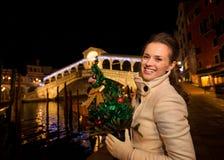 Mulher feliz com a árvore de Natal perto da ponte de Rialto em Veneza Fotos de Stock