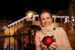 Mulher feliz com a bola do Natal perto da ponte de Rialto em Veneza Imagem de Stock Royalty Free