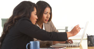 Multi-ethnic businesswomen doing research at desk Royalty Free Stock Photos
