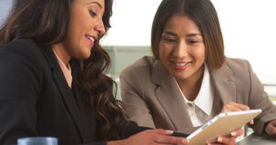 Multi-ethnic businesswomen reviewing information on tablet Stock Photo