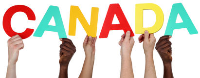 Multi ethnic group of people holding the word Canada Royalty Free Stock Images