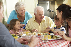 Multi Generation Family Eating Meal Together In Kitchen Stock Photo