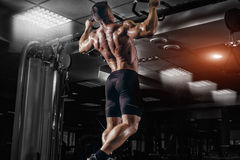 Muscle athlete man in gym making pull up Royalty Free Stock Photos