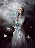 Night. Woman in  Mysterious Forest launching handmade paper Cranes. Origami Stock Photography
