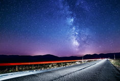 Night sky with milky way and stars. Night road illuminated by car Royalty Free Stock Photography