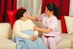 Nurse put a pillow to senior woman Stock Images