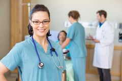 Nurse Smiling Against Patient And Medical Team In Royalty Free Stock Photo