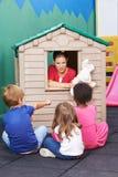Nursery teacher using playhouse for theater play Royalty Free Stock Image