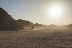Off road vehicle traveling through arid desert landscape Royalty Free Stock Photo