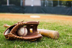 Old Baseball, Glove, and Bat on Field Stock Photo