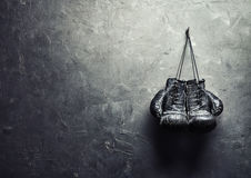 Old boxing gloves hang on nail on texture wall Royalty Free Stock Image