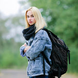 Outdoors portrait of a young beautiful blonde woman in jeans with a big old backpack Royalty Free Stock Photography