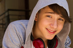 Outside portrait of teen boy. Handsome teenager carrying backpack on one shoulder and smiling, communicating by phone. Royalty Free Stock Photography