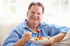 Overweight Man Sitting On Sofa Eating Bowl Of Fresh Fruit Royalty Free Stock Image