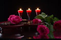 Pâtisserie rose de chocolat d'Ann de roses sur un plateau en forme de coeur Bougies Photographie stock