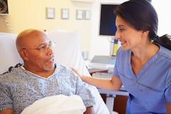 Paciente masculino de Talking To Senior de la enfermera en sitio de hospital Fotos de archivo