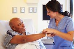 Paciente masculino mayor de Putting Wristband On de la enfermera en hospital Imagen de archivo libre de regalías