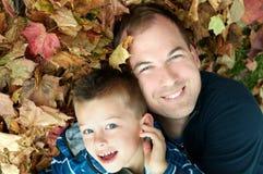 Pai e filho nas folhas Fotos de Stock