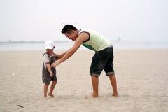 Pai e filho que jogam na praia Imagens de Stock