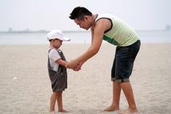Pai e filho que jogam na praia Foto de Stock