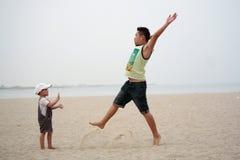 Pai e filho que jogam o salto na praia Fotografia de Stock Royalty Free
