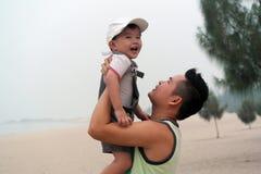 Pai Hugs Son na praia Foto de Stock
