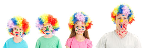 Painted faces clown wigs on family of dad and kids Stock Photo