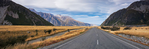 Panoramic view of long road to Mount Cook, New Zealand during autumn season. Leading line, empty road. Not centered. Royalty Free Stock Photography