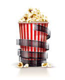 Paper container full of popcorn with film tape cinema concept Royalty Free Stock Image