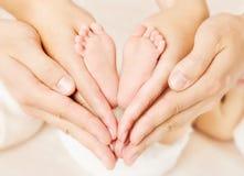 Parents nouveau-nés de pieds de bébé se tenant dans des mains. Photographie stock