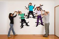 Parents sticking children to wall joke Royalty Free Stock Photo