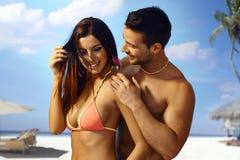Pares atractivos en la playa Fotografía de archivo libre de regalías