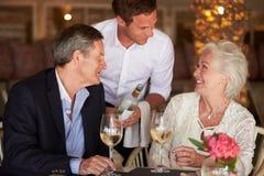 Pares mayores de Serving Wine To del camarero en restaurante Imagenes de archivo